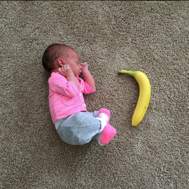 Una madre registra el crecimiento de su bebé comparando su tamaño con objetos cotidianos