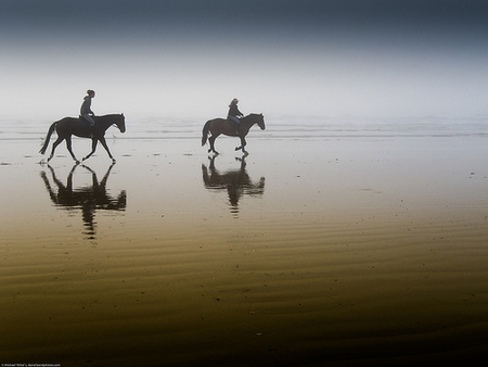 Two equestrian riders, girls on horseback, in low tide reflections de mikebaird