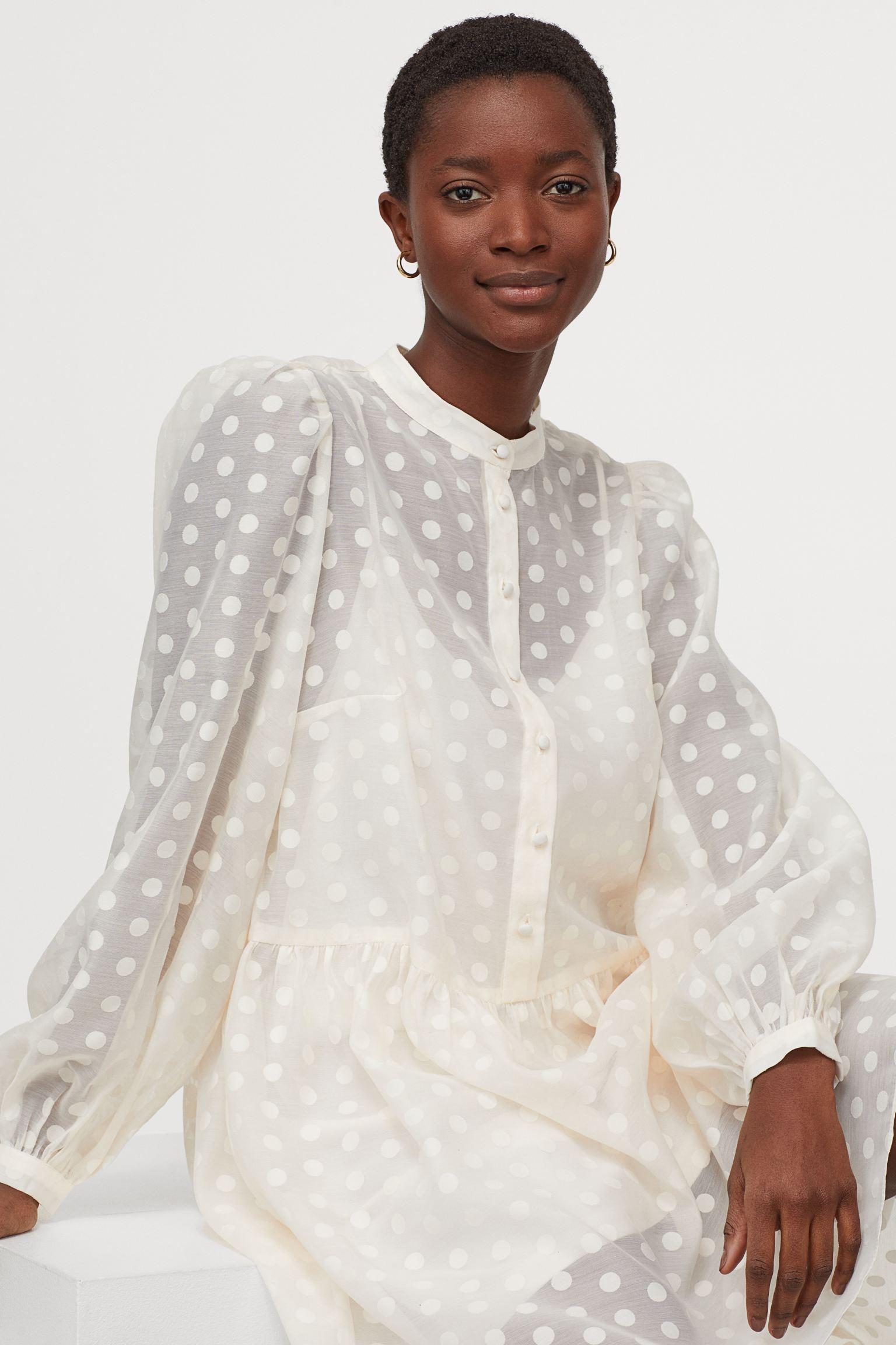 Vestido corto en tejido vaporoso con cuello elevado corto, abertura de pico y botones revestidos en la parte superior.