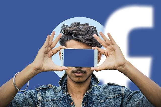 Hombre con teléfono tapando sus ojos de color azul detrás logotipo de facebook.