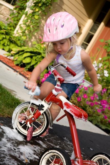 niña limpiando bicicleta