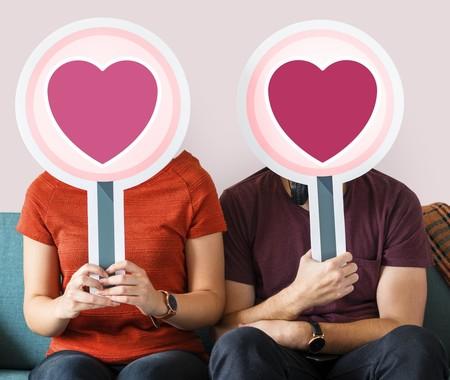 pareja tapándose la cara con cartulinas de corazón
