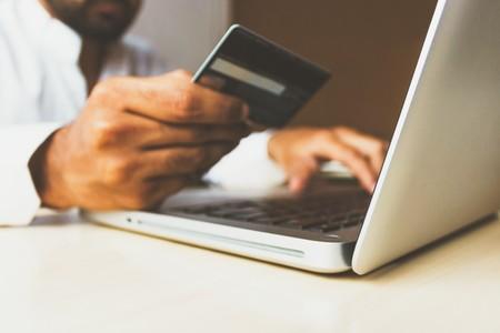 Señor comprando online con un ordenador y una tarjeta de crédito en la mano