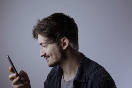 Un hombre sonrie mientras mira su móvil.