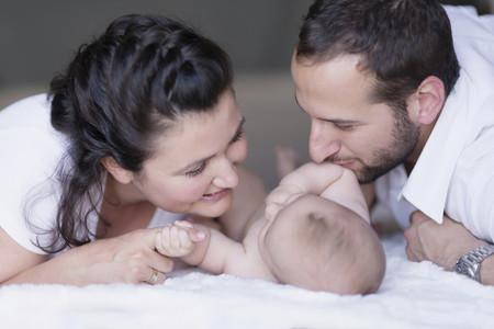 Padre y madre besando a su bebé