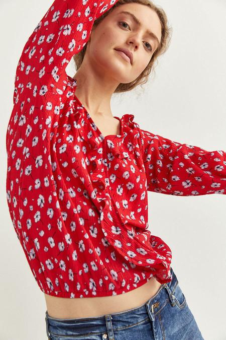 Blusa de manga 7/8s con cuello en uve, detalle de volantes y goma en puños y bajo.