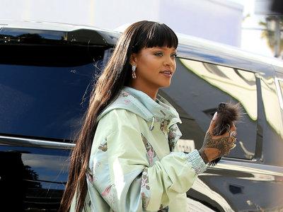 ¡Rihanna vuelve a liarla! Ahora con una maxi raja en su chubasquero-vestido y su adoradas deportivas con tacón