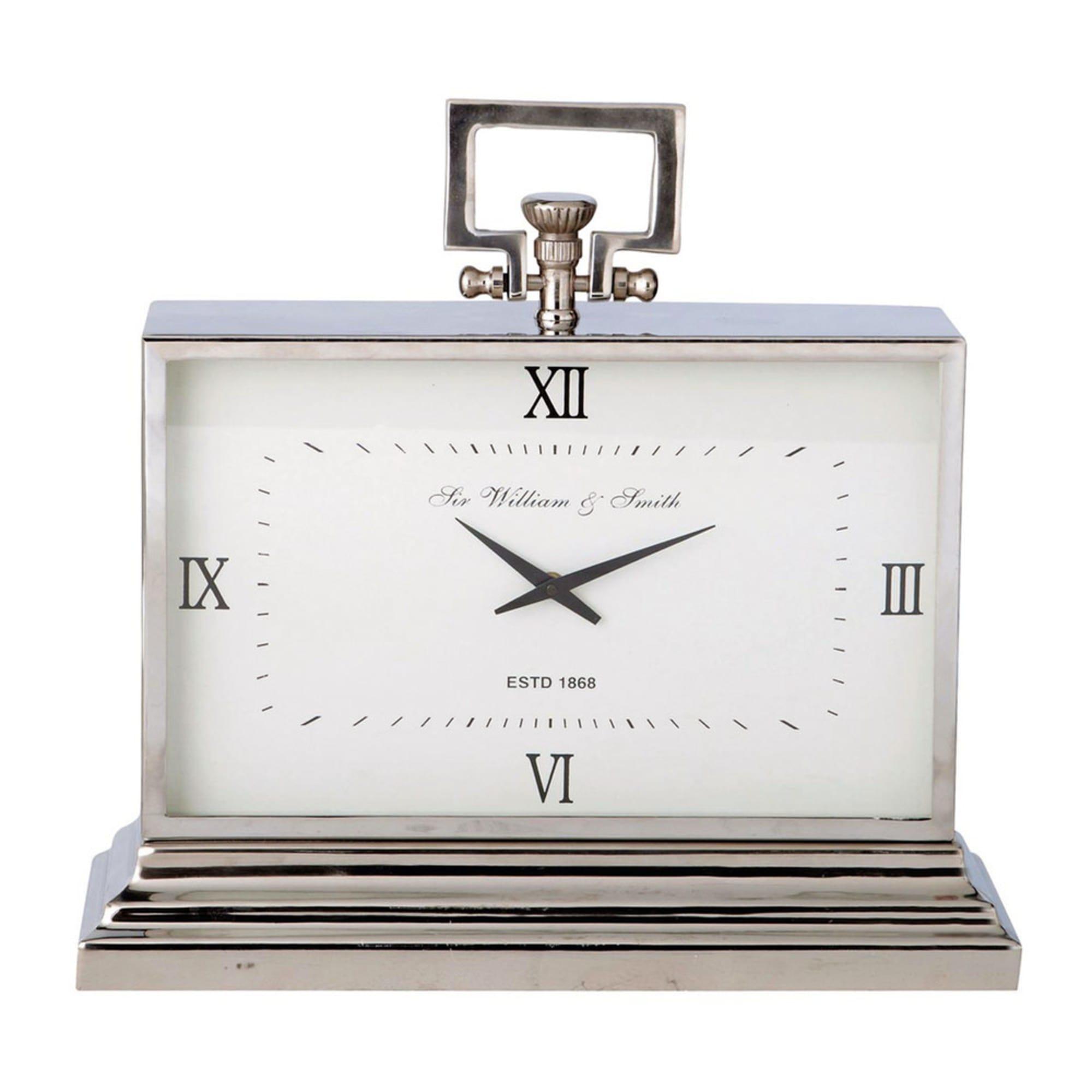 Este reloj de metal con efecto cromado presenta un diseño moderno y depurado. Un reloj de metal grande con esfera de números romanos para colocar sobre una mesa.