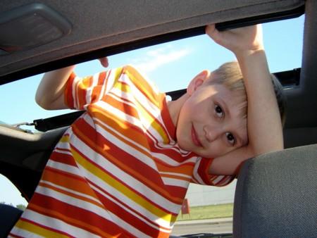 Chico refrescándose dentro del vehículo