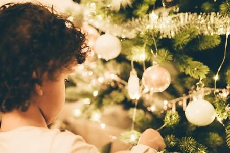 niño adornando árbol de navidad
