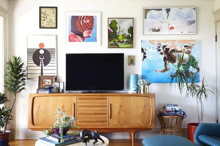 Mueble de tv rodeado de cuadros coloridos
