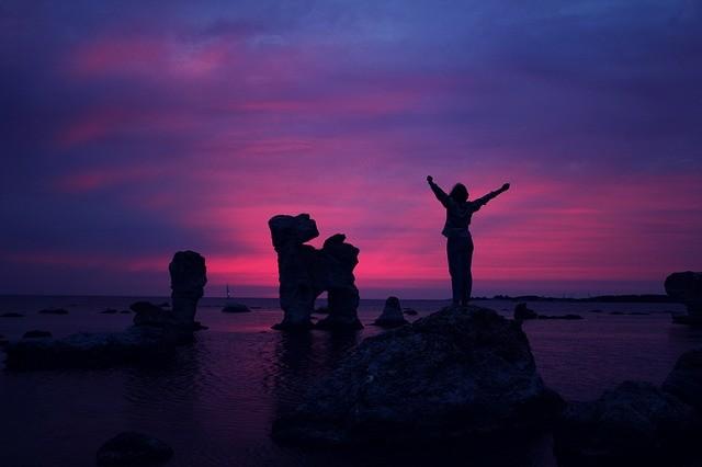 Mujer haciendo la señal de la victoria sobre una roca.