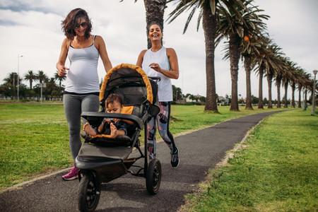 Embarazada corriendo con bebé en una sillita