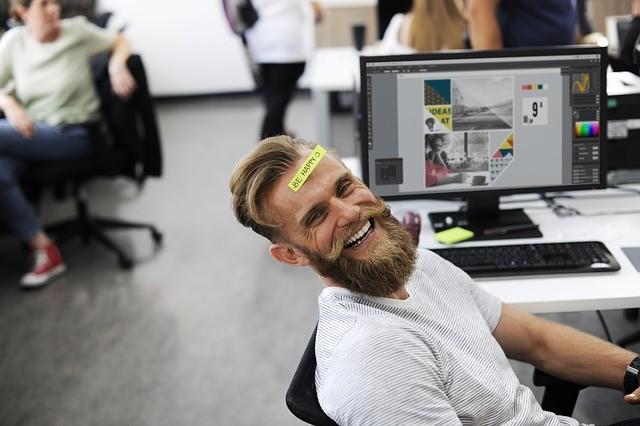 Hombre rubio con barba sonríe sentado delante de un ordenador.