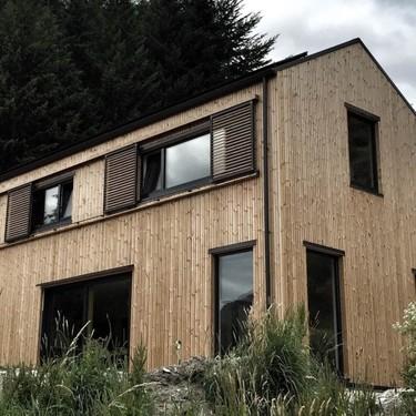 Una moderna casa en Nueva Zelanda decorada con muebles que tiene medio planeta