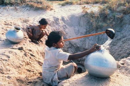 Niñas recogiendo agua de un pozo