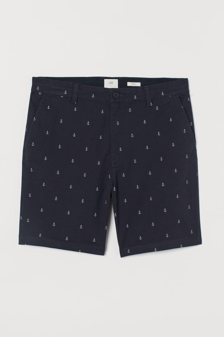 Chinos cortos en sarga elástica de algodón con cintura estándar elástica y cordón de ajuste. Bolsillos al bies, bolsillos traseros ribeteados y cierre de cremallera con botón.