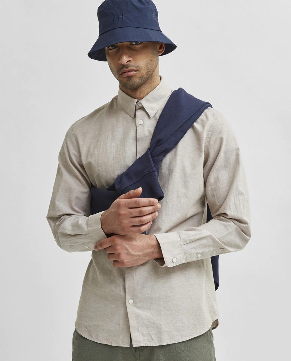 Camisa con algodón orgánico slim fit de color beige lisa. Tiene cuello clásico y puños redondeados. Ligera de algodón orgánico y lino con una textura muy suave.