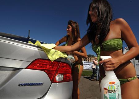 Chicas en bikini lavan coches hibridos