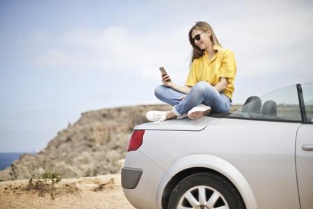 Mujer sentada encima del coche mirando el movil