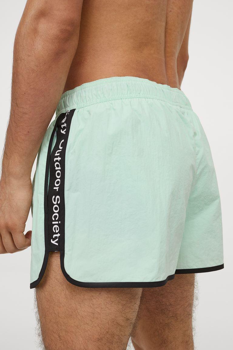 Bañador de tela con franjas laterales a contraste, cintura elástica con cordón de ajuste y bolsillos en las costuras laterales. Pantaloncillo interior de malla.