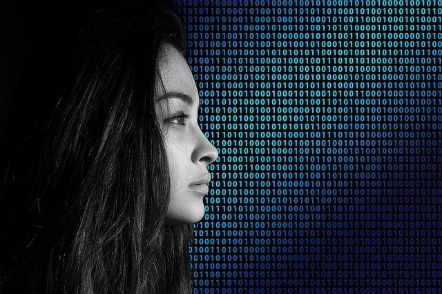 Chica morena de perfil y de fondo código binario.