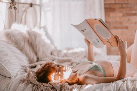 chica en la cama al amanecer, leyendo