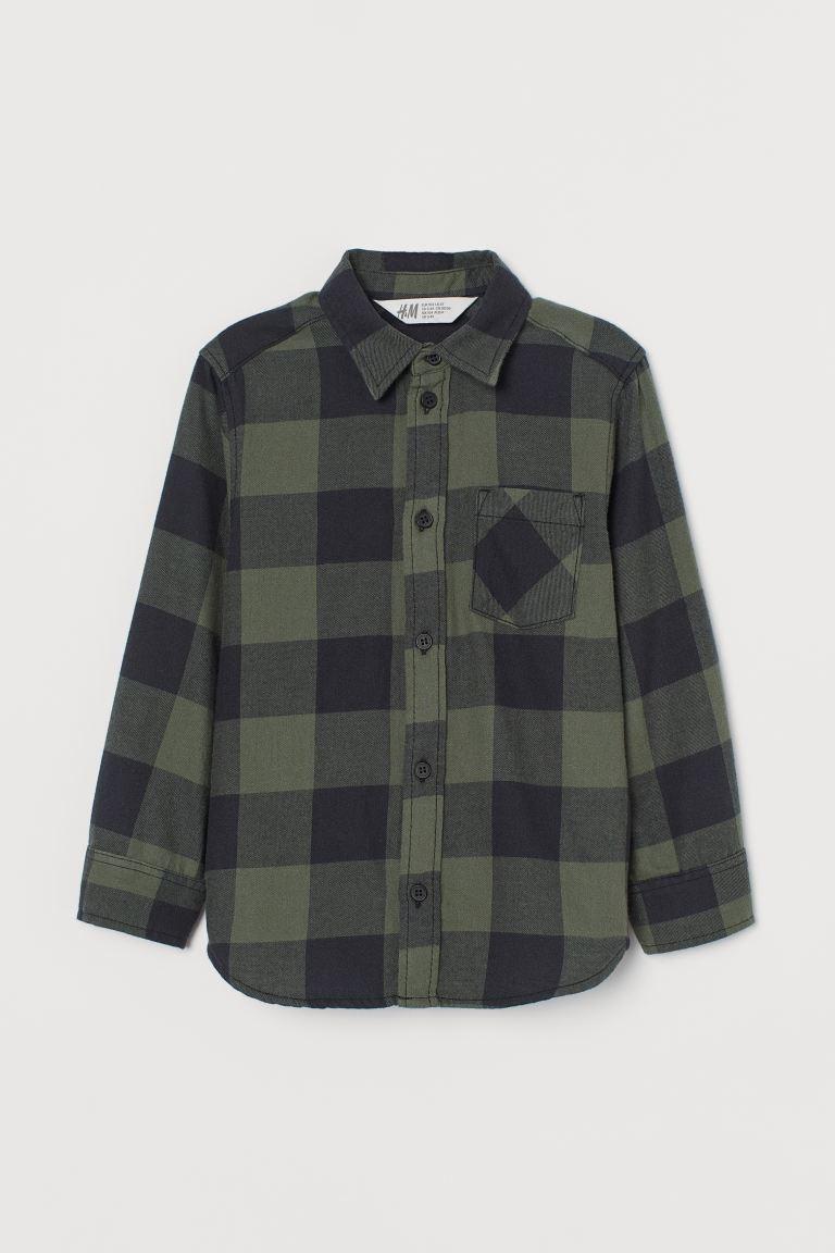 Camisa en franela de algodón suave con cuello, botones delante y canesú de doble capa con costura en la espalda. Un bolsillo superior abierto, mangas largas con puños sencillos y bajo redondeado.