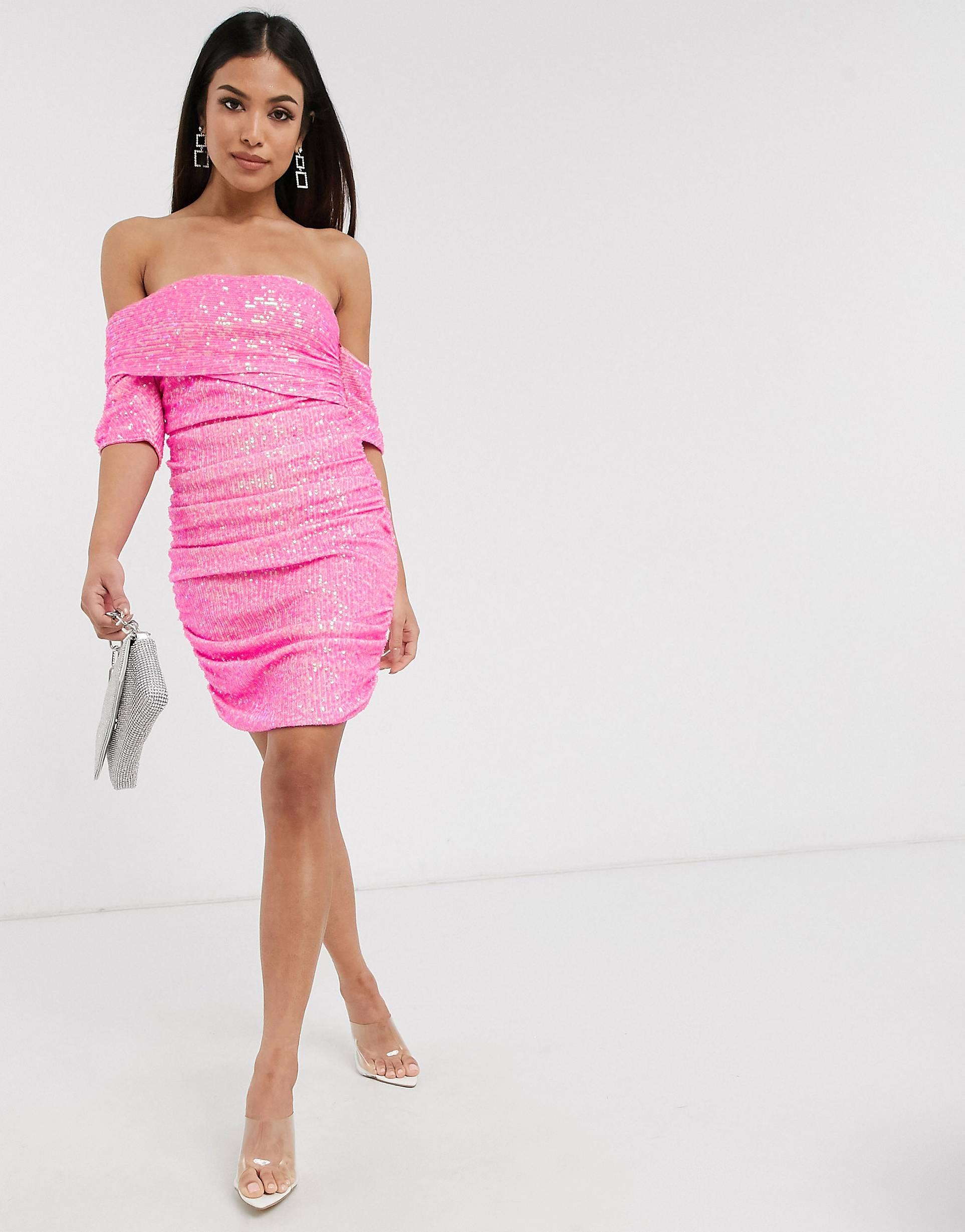 Vestido corto rosa neón con escote asimétrico y diseño drapeado de lentejuelas.