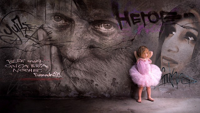 Graffiti en la pared y una niña vestida de rosa apoyada en él.