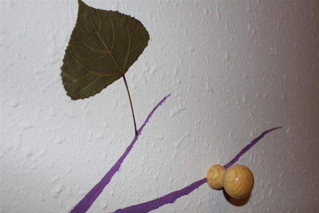 Detalle árbol perchero en la pared