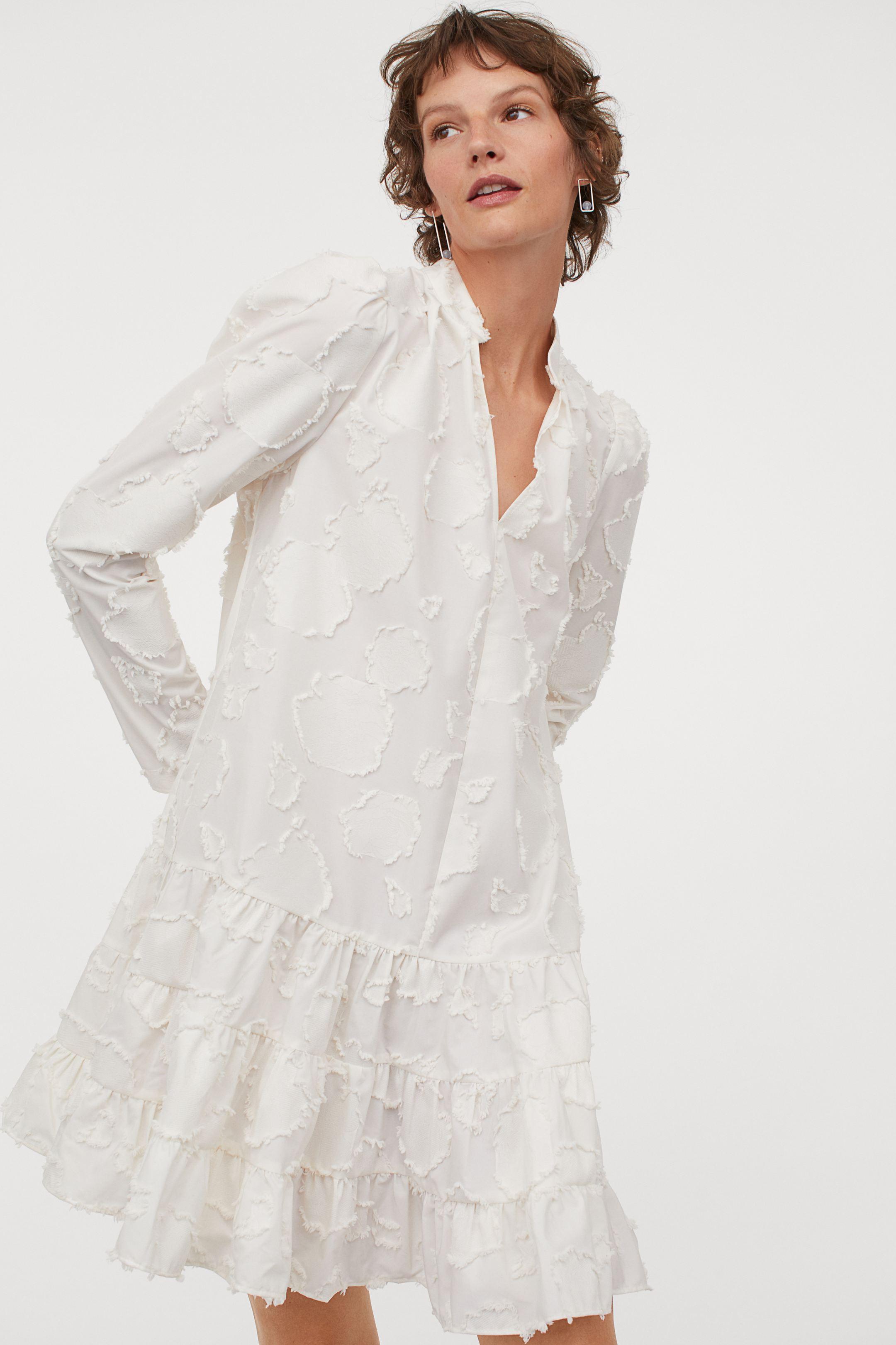 Vestido evasé ideal en color blanco con falda de volantes