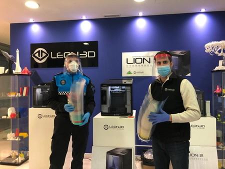 Un agente de la Policía Local de León recoge viseras impresas en 3D con láminas de acetato.