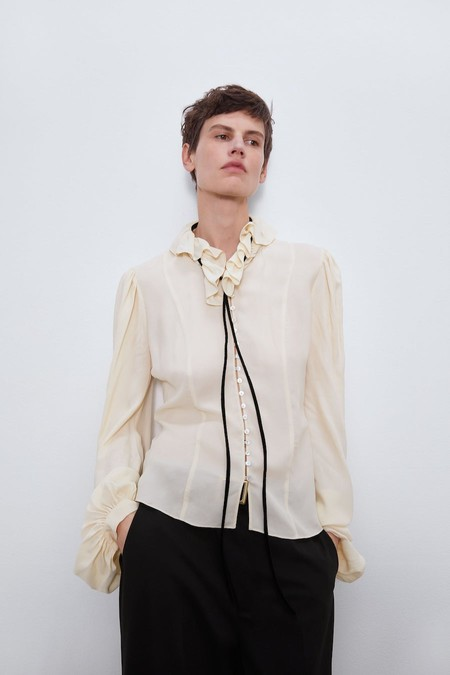 Blusa semitransparente de cuello redondo con volante.
