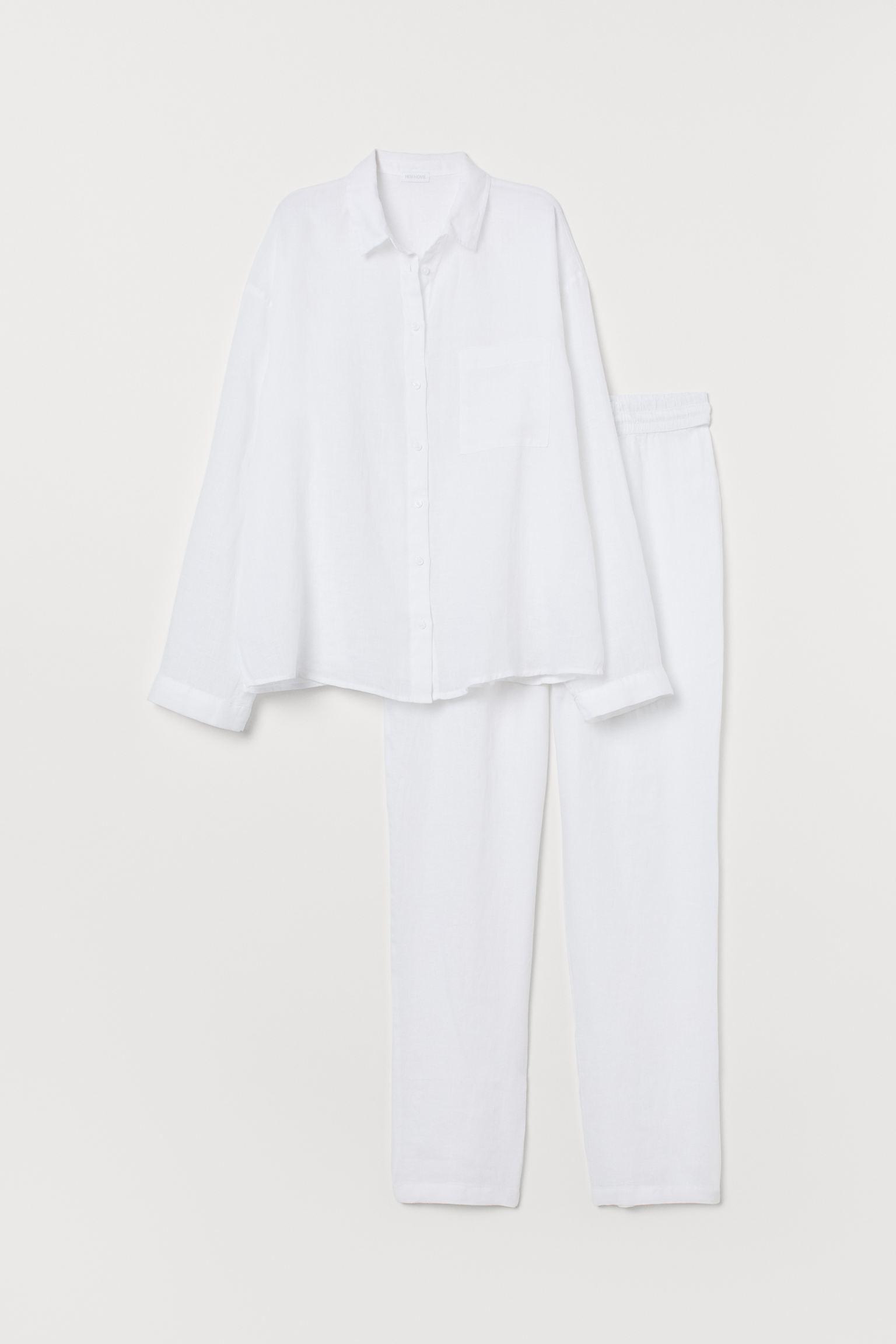 Pijama de dos piezas en lino. Camisa con cuello inglés, botones delante y un bolsillo superior abierto. Pantalón amplio con elástico revestido y cordón de ajuste en la cintura.