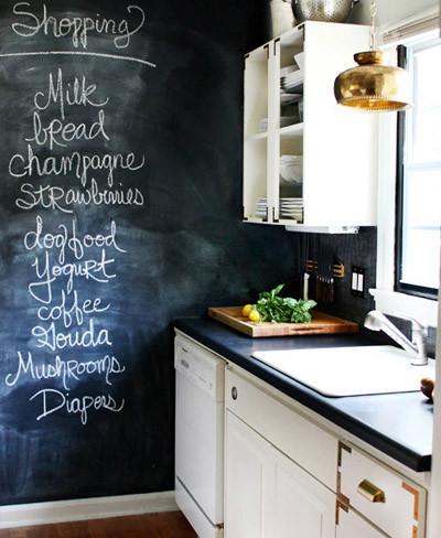 Una pequeña cocina con una gran pared de pizarra