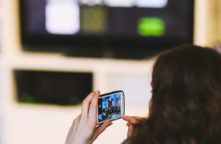 Usando el smartphone viendo la televisión