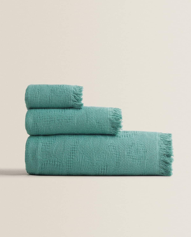 Toalla de algodón con jacquard floral y flecos. Gramaje: 550 gr/m².