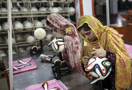 Dos empleadas de una fábrica de Pakistán dan los últimos retoques a varios balones de fútbol oficiales para el Mundial de Brasil