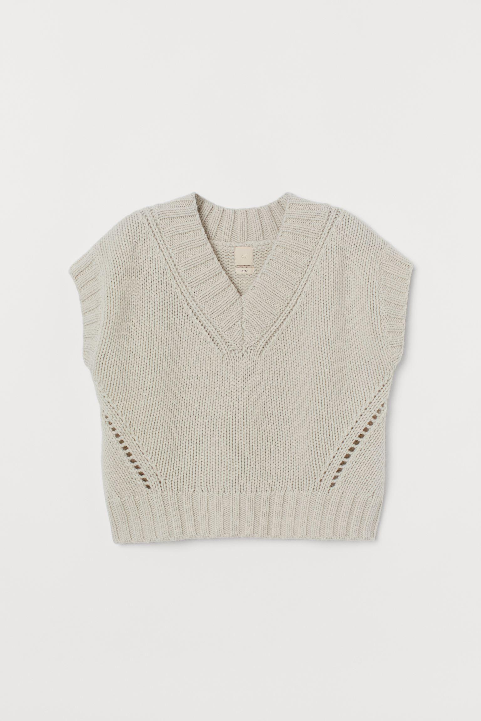 Chaleco en punto grueso de lana suave. Modelo con escote de pico, detalles en punto calado y ribete de canalé en cuello, sisas y bajo.