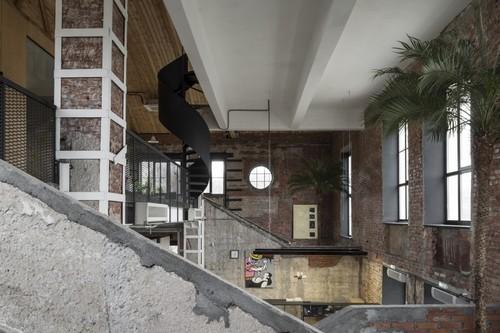 Las nuevas oficinas del museo Garage en Moscú se han instalado en un edificio que ha tenido muchas vidas antes, algunas de las cuáles se pueden intuir entre sus paredes en bruto