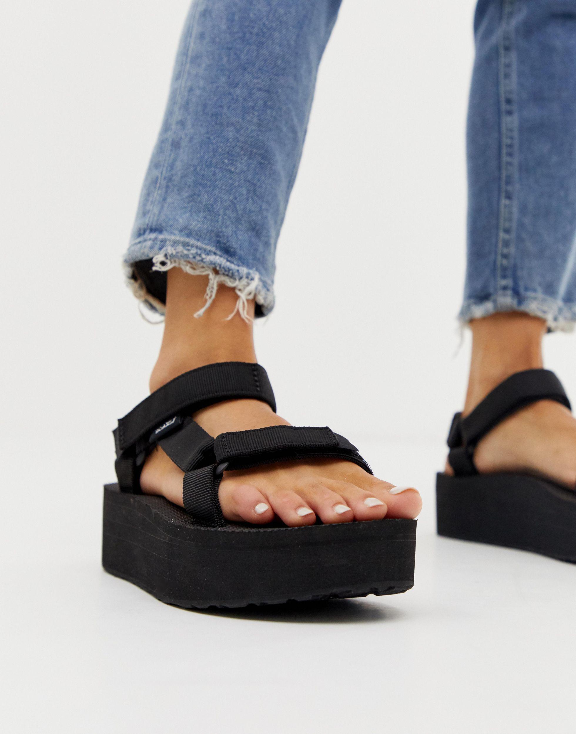 Sandalias gruesas con plataforma plana en negro.