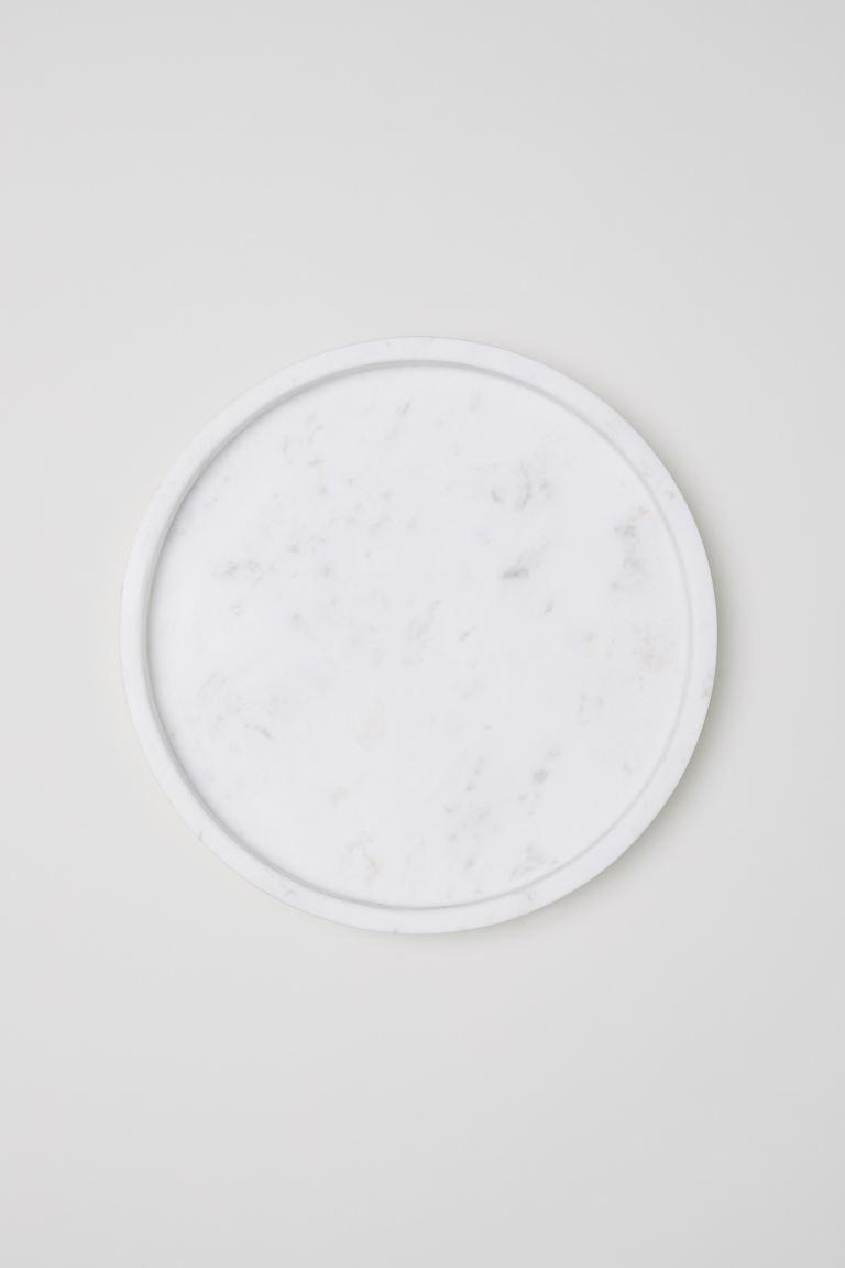 Bandeja redonda de mármol con un pequeño borde. Tacos de silicona en la parte inferior. Alto 2,5 cm. Diámetro 25,5 cm.
