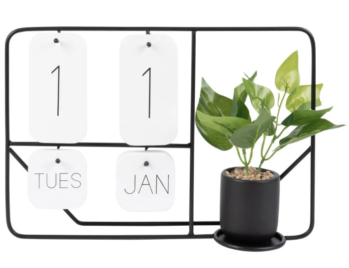 Figura de calendario de metal negro y planta artificial