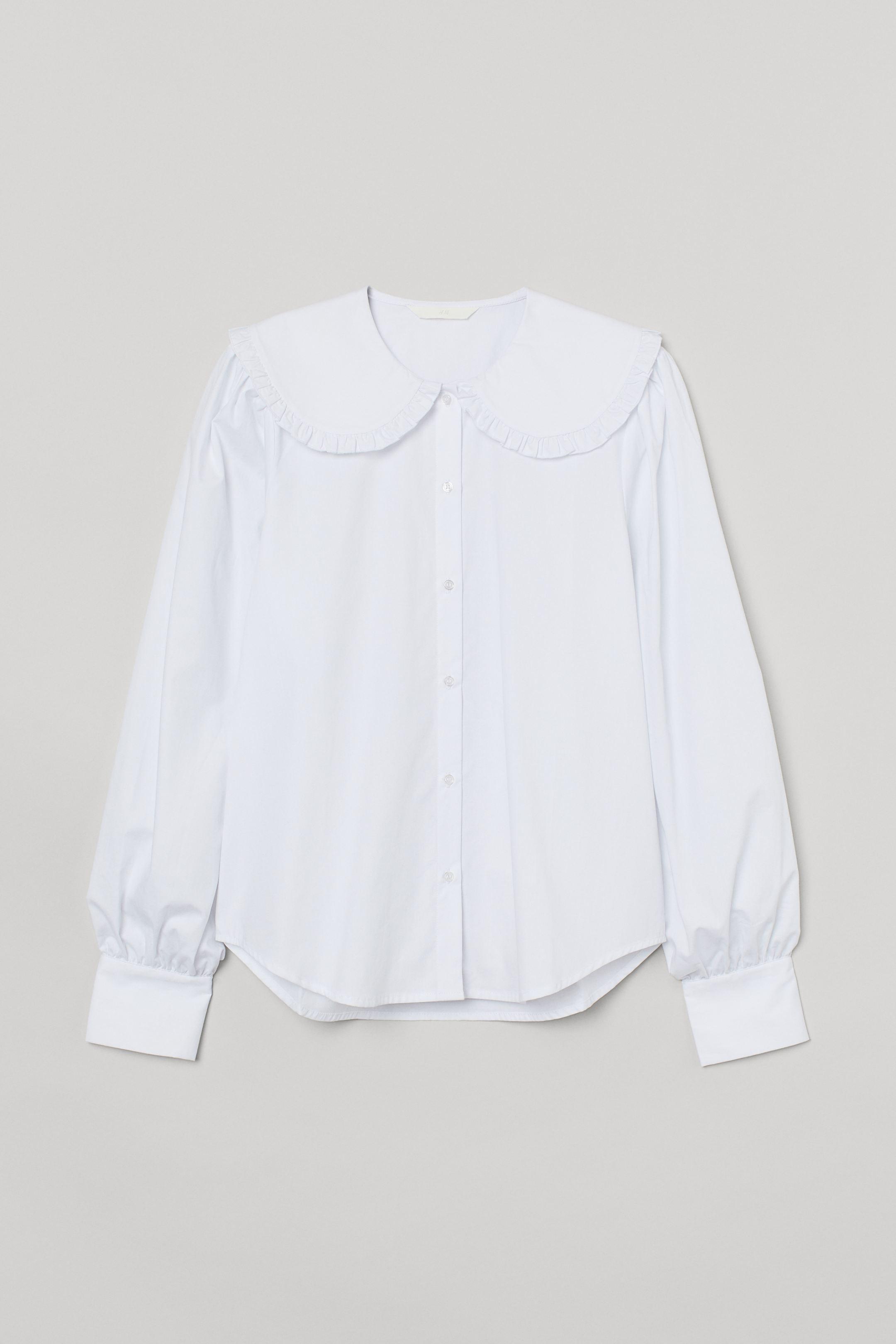 Blusa vaporosa de algodón con cuello amplio doble ribeteado con volante y cierre de botones. Modelo de corte recto con mangas largas, puños amplios abotonados y bajo redondeado con espalda algo más larga.