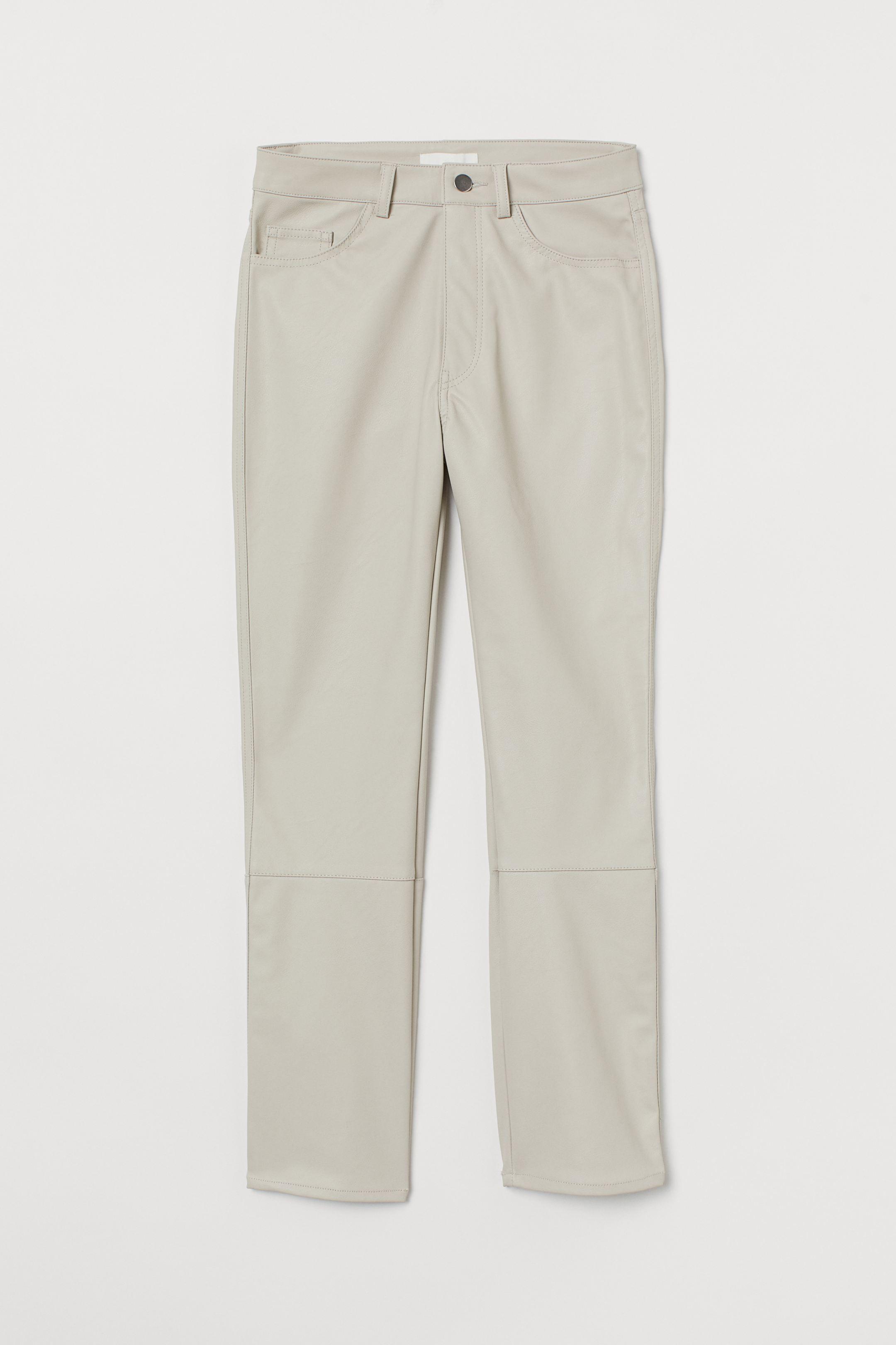 Pantalón tobillero de cinco bolsillos en piel sintética. Modelo de talle alto con cierre de cremallera con botón y perneras rectas con costuras sobre las rodillas.