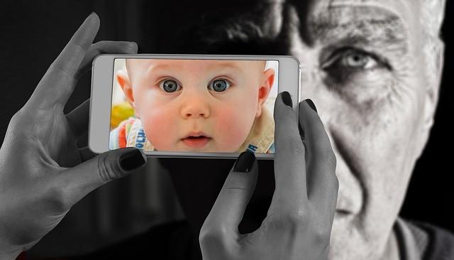 Teléfono con imagen de bebé y en 2.º plano un hombre mayor.