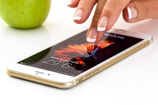 Smartphone y mano de mujer sobre la pantalla.