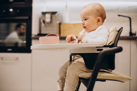 Baby Girl Sitting In Chair And Eating Porriage