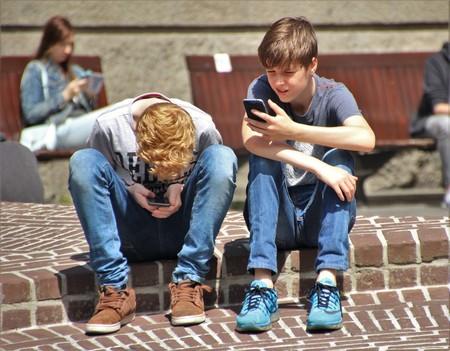 Dos chicos mirando sus teléfonos
